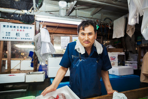 A traditional fresh fish market in Tokyo. A man in a blue apron standing behind the counter of his sの写真素材 [FYI02255393]