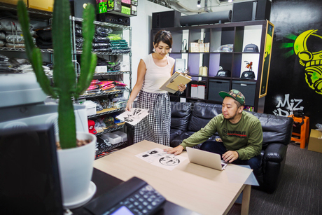 Design Studio. Two people in an office stockroom, looking at designs. Stock of clothes and hats on tの写真素材 [FYI02255395]