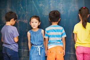 A group of children in school. Four children standing by the blackboard.の写真素材 [FYI02255399]