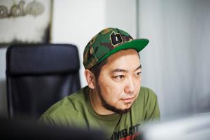 Design Studio. A man wearing a baseball cap looking at a screen.の写真素材 [FYI02255410]