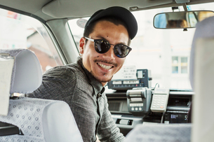 A man wearing sunglasses and baseball hat in the passenger seat of a car turning around and smiling.の写真素材 [FYI02255420]