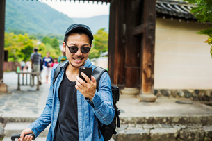 A man in sunglasses looking at his smart phone.の写真素材 [FYI02255423]