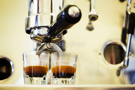 Close up of espresso machine and two glasses of espresso.の写真素材 [FYI02255426]