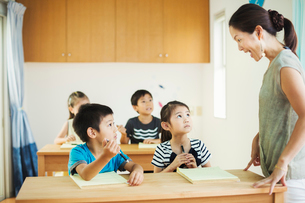A group of children in a classroom with their female teacher.の写真素材 [FYI02255445]