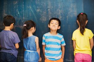 A group of children in school. Four children standing by the blackboard.の写真素材 [FYI02255450]