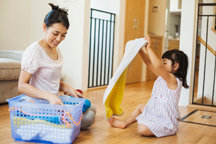 Family home. A woman and her daughter folding clean laundry.の写真素材 [FYI02255452]