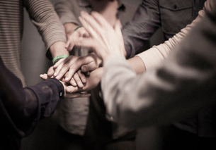 People standing with their hands layered in a team gesture.の写真素材 [FYI02255464]