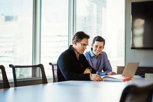 Two men at a table in a meeting room looking at a laptop computer.の写真素材 [FYI02255480]