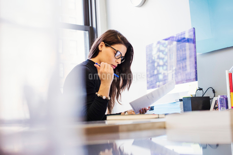 A young woman sitting at a desk in an office looking at paperwork.の写真素材 [FYI02255490]