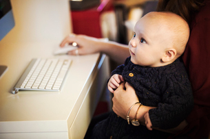 A baby seated on an adult's knee, looking at a computer screen,の写真素材 [FYI02255527]