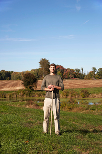 A young man in working clothes standing in a field, holding a tool.の写真素材 [FYI02255548]