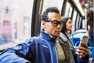 A young man and a young woman sitting on public transport looking at their cellphones.の写真素材 [FYI02255551]