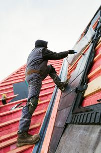A roofer replacing the tiles on a house roof.の写真素材 [FYI02255557]
