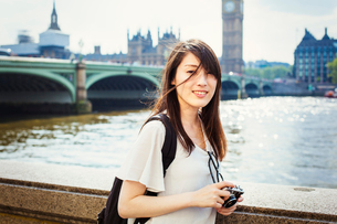 Young Japanese woman enjoying a day out in London, standing on the Queen's Walk by the River Thames.の写真素材 [FYI02255562]