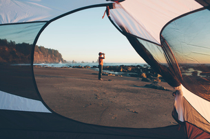 Man framed by camping tent, standing on beach and looking through binoculars at dusk, Olympic Nationの写真素材 [FYI02255564]