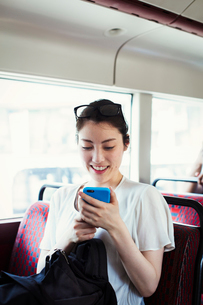 Young Japanese woman enjoying a day out in London, riding on a double decker bus.の写真素材 [FYI02255580]