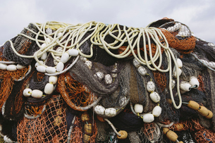 Close up of a pile of tangled up commercial fishing nets with floats attached.の写真素材 [FYI02255597]