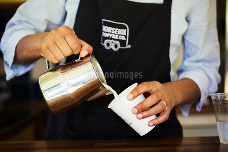 Close up of hot milk being poured from a jug into a paper cup.の写真素材 [FYI02255600]