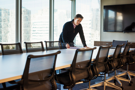 A man standing at a table in a meeting room looking down at an open book.の写真素材 [FYI02255617]