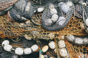 Close up of a pile of tangled up commercial fishing nets with floats attached.の写真素材 [FYI02255630]