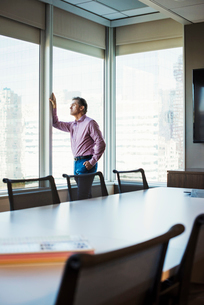 A man in a meeting room looking out of a window at an urban landscape.の写真素材 [FYI02255636]