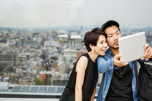 Two people, man and woman taking a selfie with a digital tablet, in front of a view over a large citの写真素材 [FYI02255642]