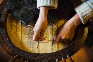 Upholstery workshop. A woman refurbishing a chair seat.の写真素材 [FYI02255645]