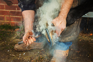 A farrier shoeing a horse, bending down and fitting a new horseshoe to a horse's hoof. Steam rising.の写真素材 [FYI02255651]