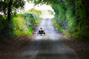 A man using a recumbent three wheeler cycle on a shady country road.の写真素材 [FYI02255674]