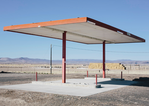 Abandoned rural gas station, hay bales in the distance,の写真素材 [FYI02255707]