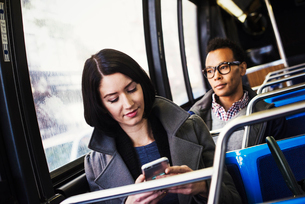 A young woman and a young man sitting on public transport, one looking at a cellphone and one lookinの写真素材 [FYI02255718]