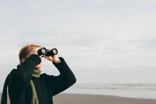 Middle aged man standing on a beach, looking through binoculars at Seabrook, Washington, USA.の写真素材 [FYI02255724]