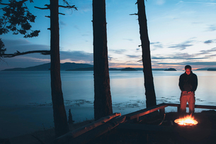 Man standing by campfire at dusk, San Juan Islands in the distance, Washington, USA.の写真素材 [FYI02255740]
