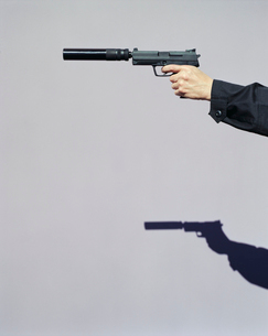 Detail of man aiming high powered hand gun with silencerの写真素材 [FYI02255760]