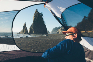 Man sitting in camping tent, Rialto Beach in distance, Olympic National Park, Washington, USA.の写真素材 [FYI02255779]