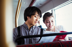 Young Japanese man and woman enjoying a day out in London, riding on a double decker bus.の写真素材 [FYI02255780]