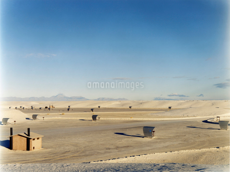 An open space a desert landscape, with a small cabin and sun shelters, surrounded by mountains.の写真素材 [FYI02255784]