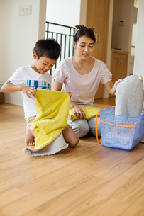 Family home. a woman and her son sorting and folding clean laundry.の写真素材 [FYI02255814]