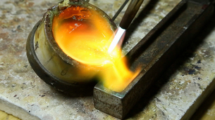 Molten metal, gold being poured into a mould for setting.の写真素材 [FYI02255821]