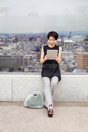 Woman using a digital tablet, with her back to the view over a large city.の写真素材 [FYI02255824]