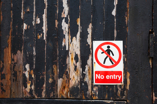 Close up of a 'No Entry' sign on a weathered wooden wall.の写真素材 [FYI02255832]