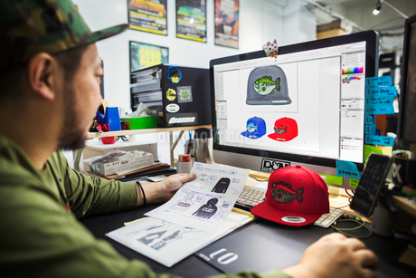 A man, a designer working on screen creating designs for baseball caps.の写真素材 [FYI02255881]