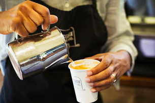 Close up of hot milk being poured from a jug into a paper cup.の写真素材 [FYI02255897]