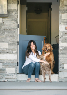 Woman sitting by her door patting her two dogs.の写真素材 [FYI02255933]