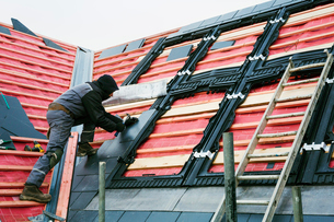 A roofer replacing the tiles on a house roof.の写真素材 [FYI02255935]