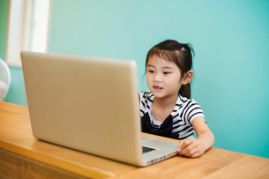 A young girl seated at a laptop computer in a classroom.の写真素材 [FYI02255979]