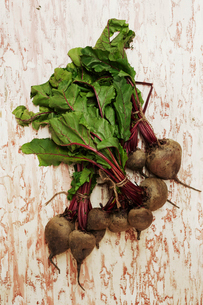 A shot of bundles of beets on a wooden surface, seen from above.の写真素材 [FYI02255986]