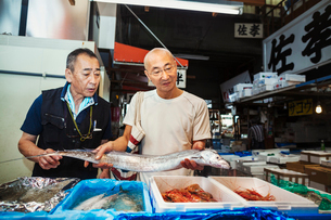 A traditional fresh fish market in Tokyo. Two men, a seller and client holding a long fish for sale.の写真素材 [FYI02256038]