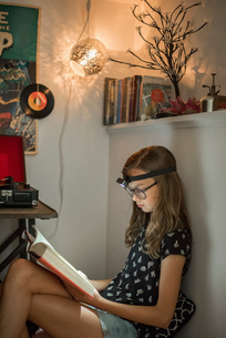 A girl reading a book in a quiet corner using a head torch.の写真素材 [FYI02256039]