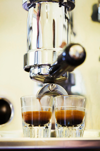 Close up of espresso machine and two glasses of espresso.の写真素材 [FYI02256049]